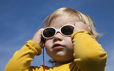 portrait of two years aged blonde happy baby yellow shirt with white kid sunglasses and blue sky background
