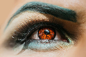 Male eye with dark eyeshadow makeup black eyebrow and orange colored decorative contact lens with serious look closeup